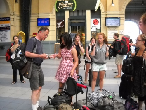 The group swarms in to get tickets to board the train back into Athens from the Piraeus.