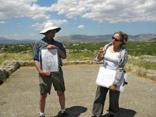 Magister Prillwitz explains how the palace at Tiryns had two megaron-like chambers. She is currently lecturing in the smaller megaron, which had a rectangular hearth and less fancy masonry compared to the main megaron. Why are there two megarons? This could be an indication of multiple tiers of government.