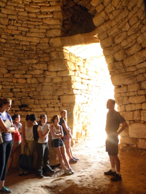 The group examines the construction of the tholos. Unfortunately this tomb was robbed, and what remains is a Roman wine press.
