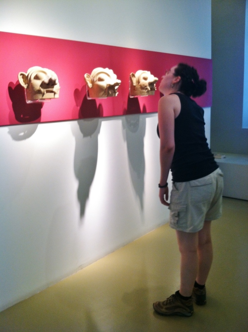 Catherine D. examines some strange masks in the Naupflion Museum that were found at Tiryns.  These masks likely belong to a Greek Geometric-Period cult.
