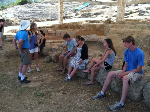 Students sit on the remains of Hellenistic-period temples while listening to Prof. Rutter explain the excavations of the site of Ancient Aigeira.