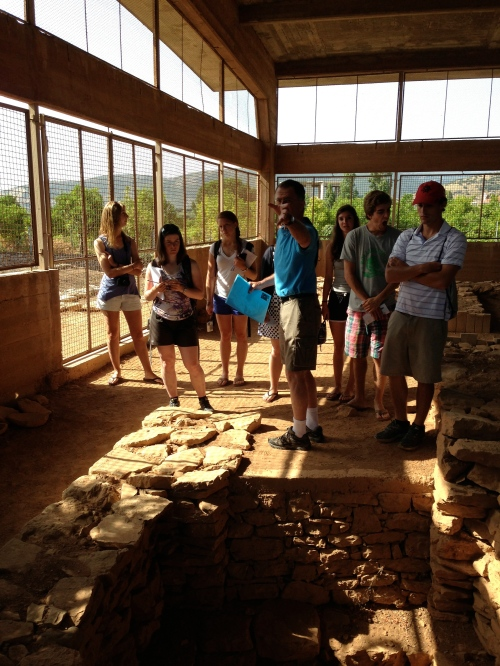 """Prof. Rutter gives the group a lecture on the EH II-period House of the Tiles at Lerna, an example of one of the monumental EH II """"corridor houses."""" This particular corridor house—the first corridor house discovered—was associated with finds of a large number of fallen tiles that once made up the roof of the structure."""