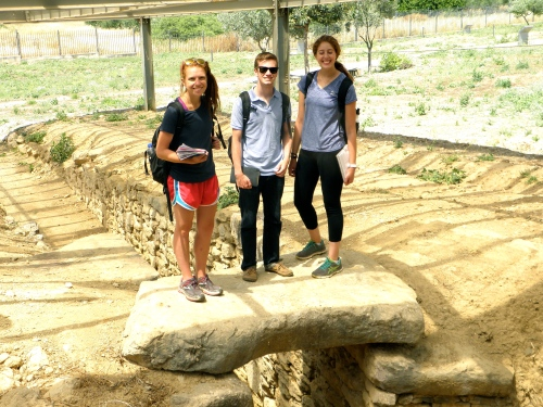 Catherine, Brett, and Laura standing on the lintel block of the largest tholos tomb at Dendra in the Argive plain, visible from the citadel at Midea. This lintel block indicates the original ground level from when this tomb was constructed.
