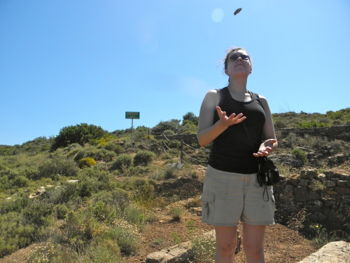 Catherine tosses a piece of silver ore that Professor Rutter found on site.