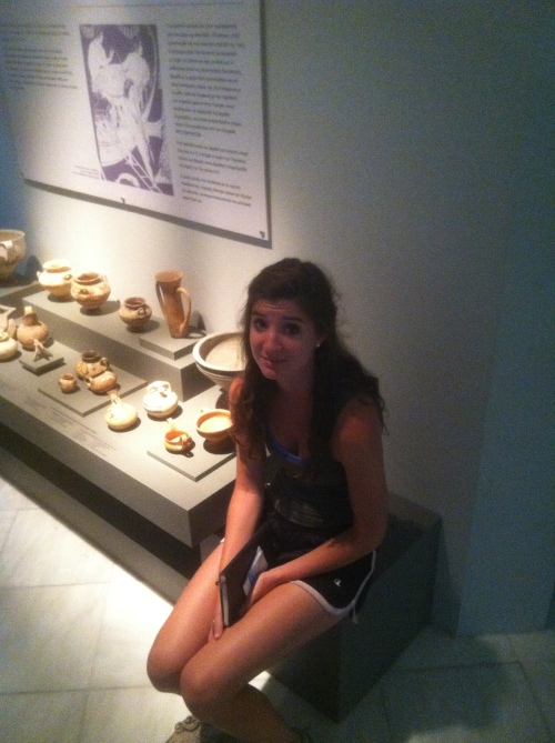 Nina takes a seat next to a display of recently-excavated pottery from the area of Volos.